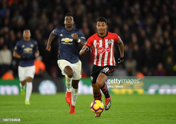 Mario Lemina of Southampton runs with the ball under pressure from Paul Pogba of Manchester United during the Premier League match between...
