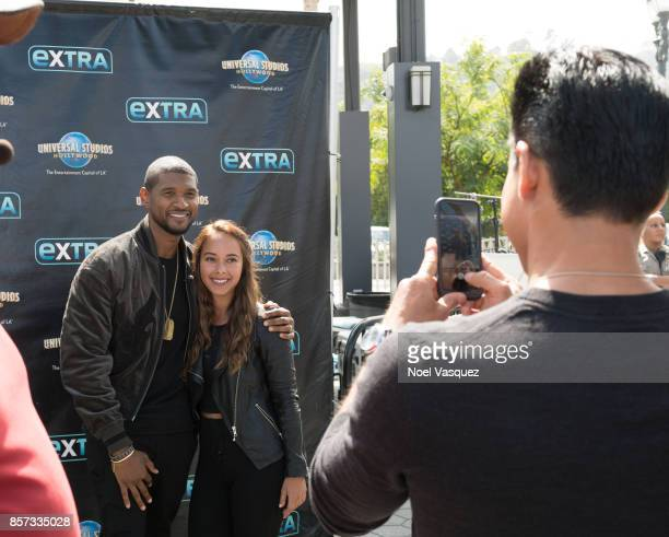 Mario Lopez takes a picture of Usher with a fan at 'Extra' at Universal Studios Hollywood on October 3 2017 in Universal City California