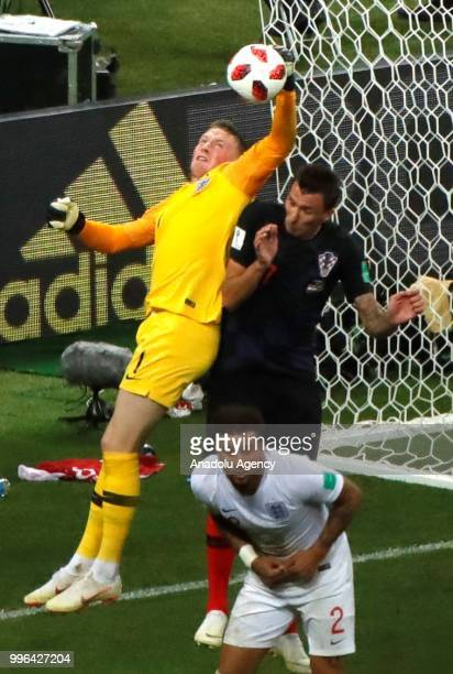 Mario Mandukic of Croatia in action against Jordan Pickford of England during the 2018 FIFA World Cup Russia semi final match between Croatia and...