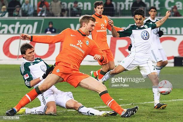 Mario Mandzukic and Josue of Wolfsburg and Per Mertesacker of Bremen battle for the ball during the Bundesliga match between VfL Wolfsburg and SV...