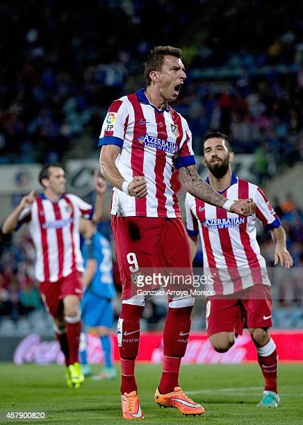 Mario Mandzukic of Atletico de Madrid celebrates scoring their opening with teammates Arda Turan and Diego Godin goal during the La Liga match...