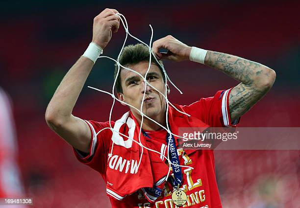 Mario Mandzukic of Bayern Muenchen celebrates with a piece of goal netting after winning the UEFA Champions League final match against Borussia...