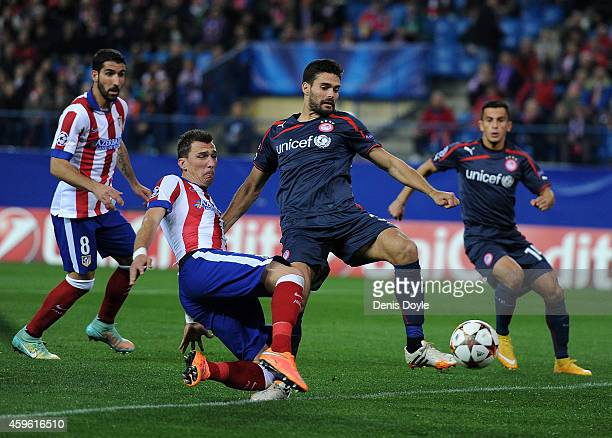 Mario Mandzukic of Club Atletico de Madrid vies for the ball with Alberto Botia of Olympiacos FC during the UEFA Champions League Group A match...