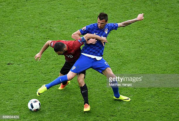 Mario Mandzukic of Croatia and Arda Turan of Turkey compete for the ball during the UEFA EURO 2016 Group D match between Turkey and Croatia at Parc...
