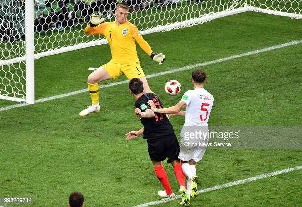 Mario Mandzukic of Croatia and John Stones of England react during the 2018 FIFA World Cup Russia semi final match between Croatia and England at the...