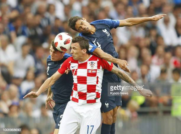 Mario Mandzukic of Croatia battles for the ball against Benjamin Pavard and Raphael Varane of France during the first half of the World Cup final at...