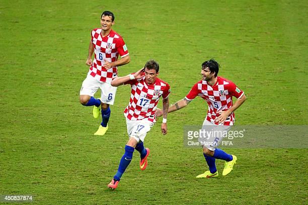 Mario Mandzukic of Croatia celebrates scoring his team's third goal with his teammates Dejan Lovren and Vedran Corluka during the 2014 FIFA World Cup...
