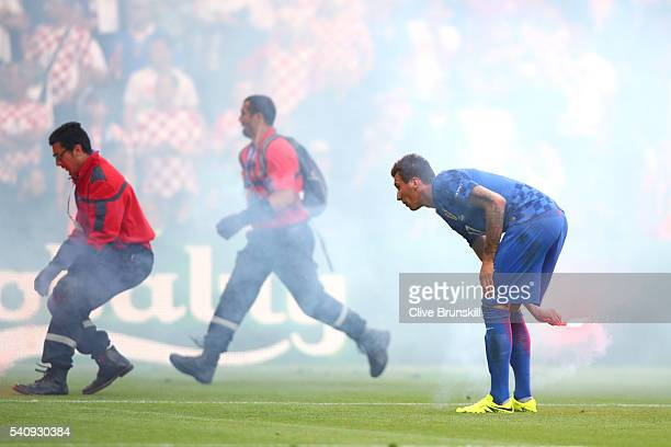 Mario Mandzukic of Croatia helps remove flares from the ptich during the UEFA EURO 2016 Group D match between Czech Republic and Croatia at Stade...