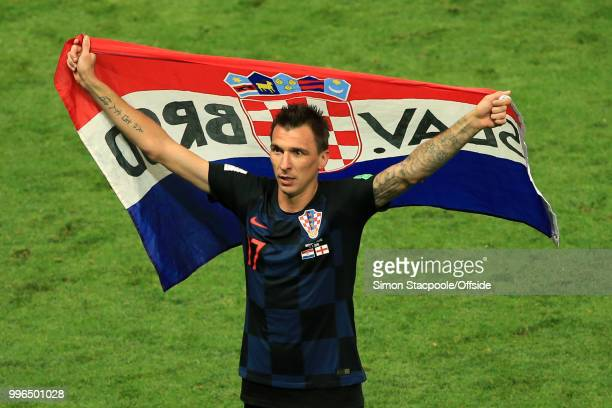 Mario Mandzukic of Croatia holds a flag aloft as he celebrates victory after the 2018 FIFA World Cup Russia Semi Final match between Croatia and...