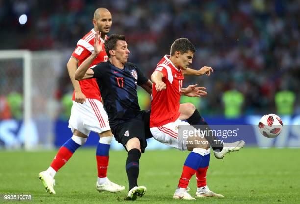 Mario Mandzukic of Croatia tackles Roman Zobnin of Russia during the 2018 FIFA World Cup Russia Quarter Final match between Russia and Croatia at...
