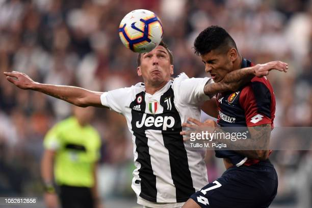 Mario Mandzukic of Juventus and Cristian Romero of Genoa jump for the ball during the Serie A match between Juventus and Genoa CFC at Allianz Stadium...