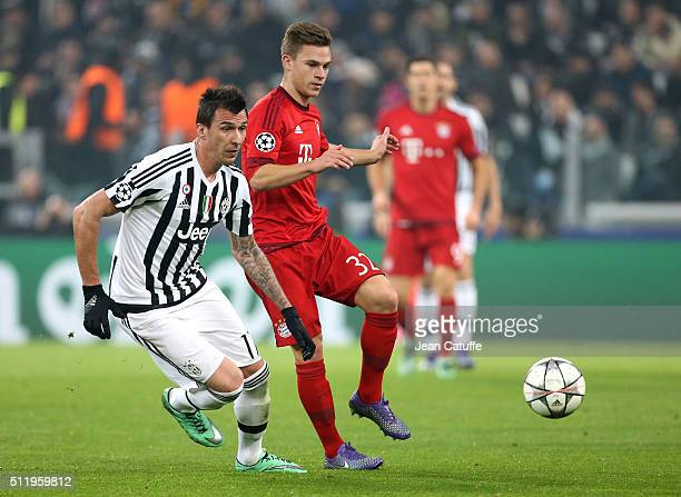 Mario Mandzukic of Juventus and Joshua Kimmich of Bayern Muenchen in action during the UEFA Champions League Round of 16 first leg match between...