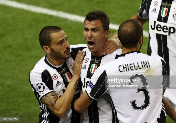 Mario Mandzukic of Juventus celebrates scoring his sides first goal with Giorgio Chiellini of Juventus and Leonardo Bonucci of Juventus during the...