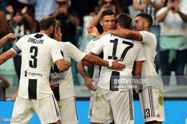 Mario Mandzukic of Juventus celebrates with teammates Emre Can and Cristiano Ronaldo after scoring the equalizer during the Serie A match between...