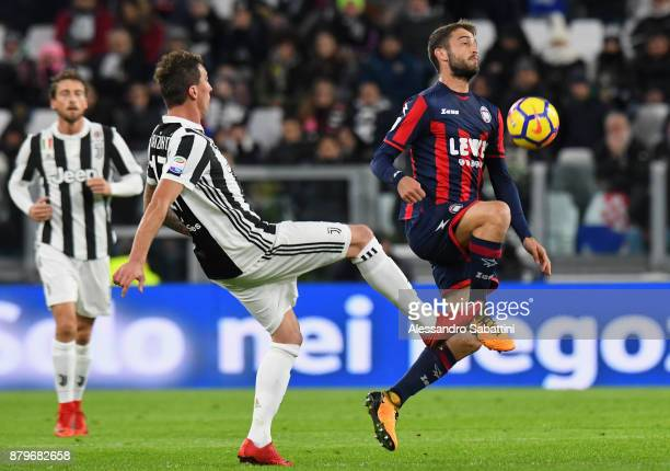 Mario Mandzukic of Juventus competes for the ball whit Andrea Barberis of FC Crotone during the Serie A match between Juventus and FC Crotone at...