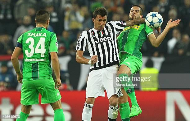 Mario Mandzukic of Juventus competes for the ball with Alvaro Dominguez and Granit Xhaka of VfL Borussia Monchengladbach during the UEFA Champions...