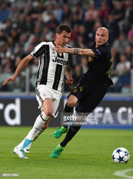 Mario Mandzukic of Juventus competes with Andrea Raggi of AS Monaco during the UEFA Champions League Semi Final second leg match between Juventus and...