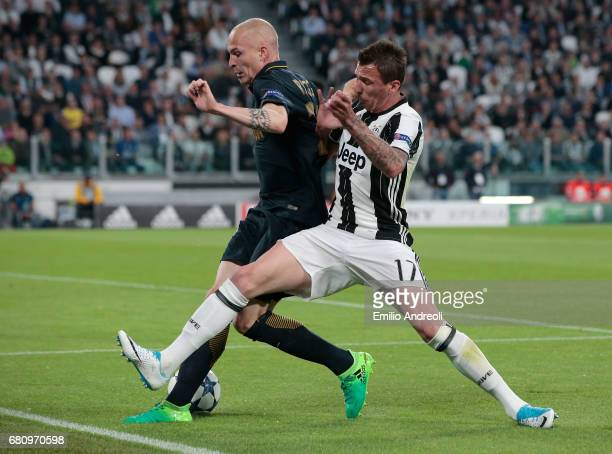 Mario Mandzukic of Juventus FC competes for the ball with Andrea Raggi of AS Monaco during the UEFA Champions League Semi Final second leg match...