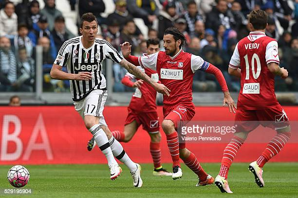Mario Mandzukic of Juventus FC is challenged by Cristian Zaccardo of Carpi FC during the Serie A match between Juventus FC and Carpi FC at Juventus...