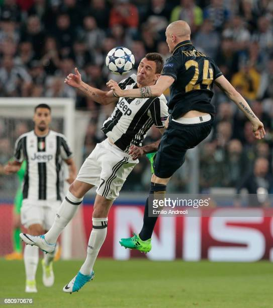 Mario Mandzukic of Juventus FC jumps for the ball with Andrea Raggi of AS Monaco during the UEFA Champions League Semi Final second leg match between...