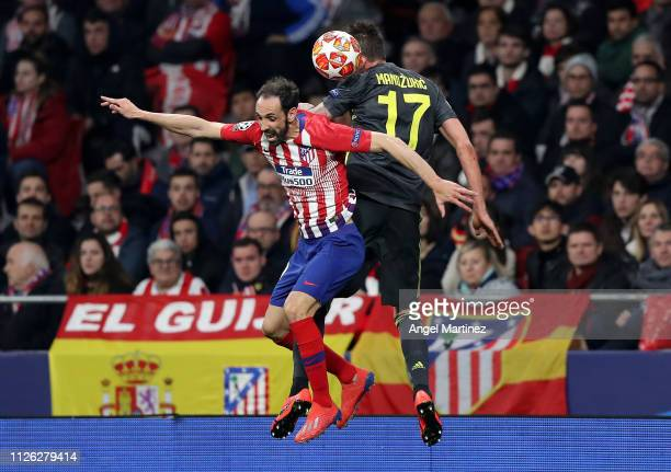 Mario Mandzukic of Juventus is challenged by Juanfran of Atletico Madrid during the UEFA Champions League Round of 16 First Leg match between Club...