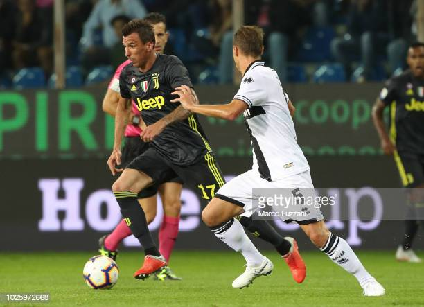 Mario Mandzukic of Juventus is challenged by Leo Stulac of Parma Calcio during the serie A match between Parma Calcio and Juventus at Stadio Ennio...