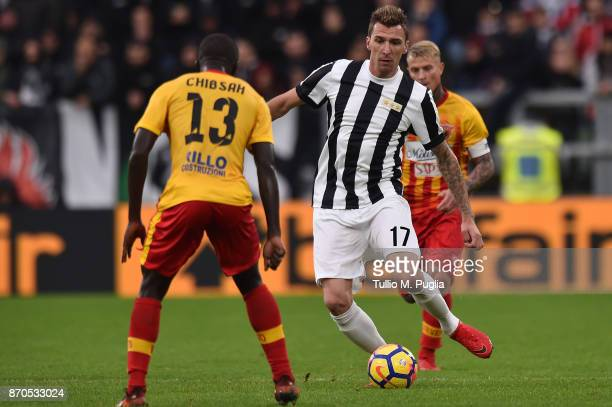 Mario Mandzukic of Juventus is challenged by Yussif Raman Chibsah of Benevento during the Serie A match between Juventus and Benevento Calcio on...