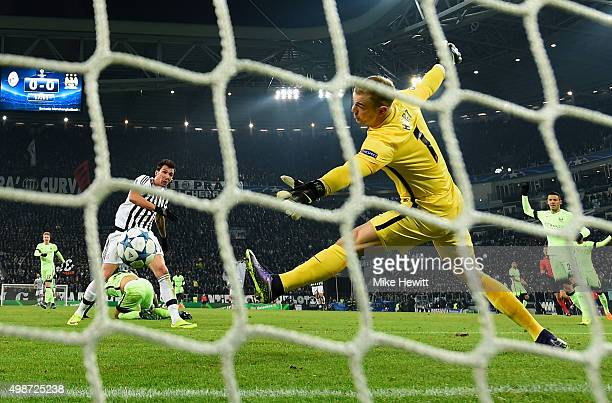 Mario Mandzukic of Juventus scores the opening goal past the outstretched Joe Hart of Manchester City during the UEFA Champions League group D match...