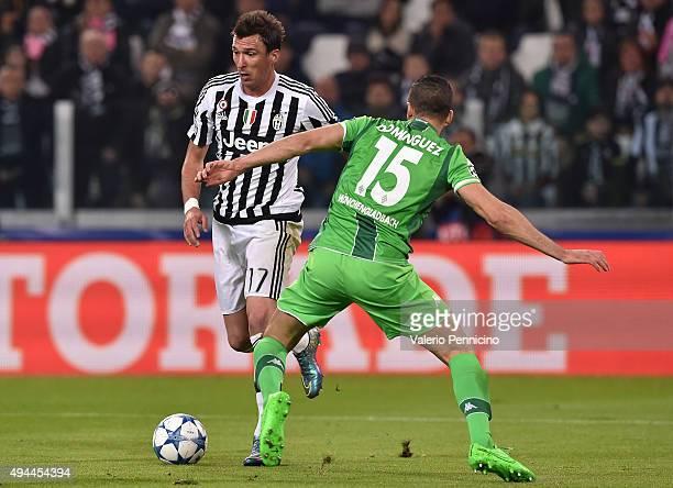 Mario Mandzukic of Juventus turns Alvaro Dominguez of VfL Borussia Monchengladbach during the UEFA Champions League group stage match between...