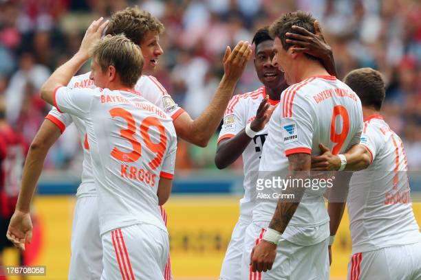 Mario Mandzukic of Muenchen celebrates his team's first goal with team mates Toni Kroos Thomas Mueller David Alaba and Philipp Lahm during the...