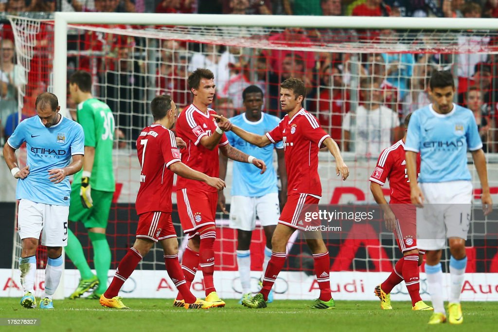 Mario Mandzukic of Muenchen celebrates his team's second goal with team mates Franck Ribery and Thomas Mueller during the Audi Cup Final match between FC Bayern Muenchen and Manchester City at Allianz Arena on August 1, 2013 in Munich, Germany.