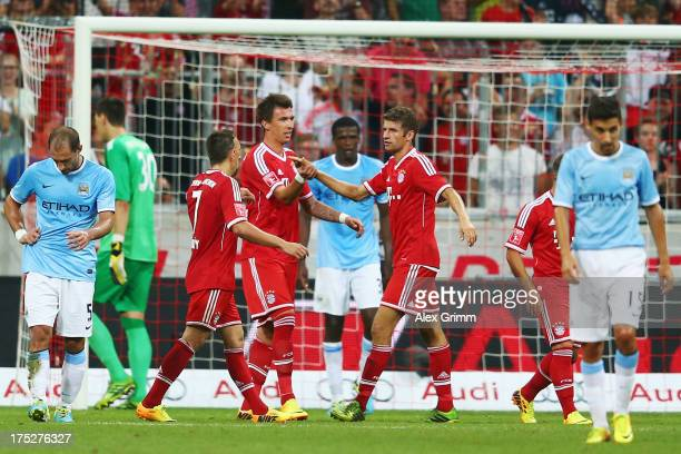 Mario Mandzukic of Muenchen celebrates his team's second goal with team mates Franck Ribery and Thomas Mueller during the Audi Cup Final match...