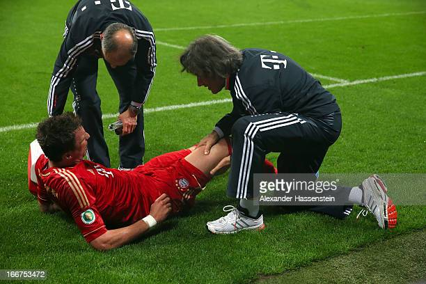 Mario Mandzukic of Muenchen receives medical threatment from team doctor HansWilhelm MuellerWohlfahrt after scoring the opening goal during the DFB...