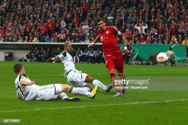 Mario Mandzukic of Muenchen scores the opening goal against Alexander Madlung of Wolfsburg and his team mate Naldo during the DFB Cup Semi Final...