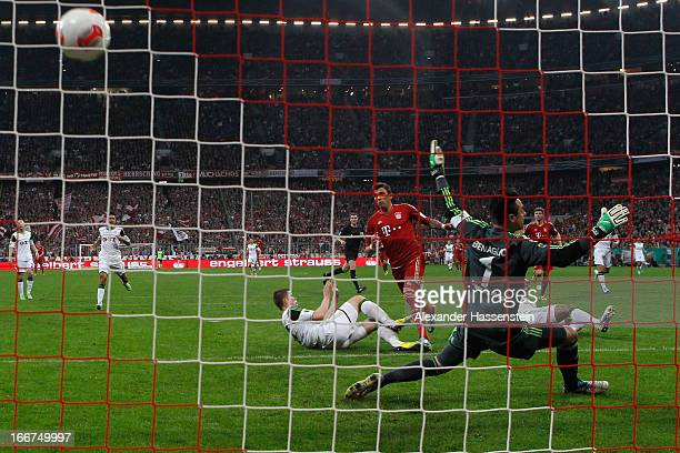 Mario Mandzukic of Muenchen scores the opening goal against Alexander Madlung of Wolfsburg and his keeper Diego Benaglio during the DFB Cup Semi...