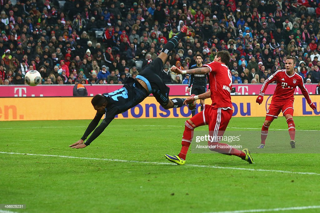Mario Mandzukic (C) of Muenchen scores the opening goal against Jonathan Tah (L) of Hamburg during the Bundesliga match between FC Bayern Muenchen and Hamburger SV at Allianz Arena on September 28, 2013 in Munich, Germany.