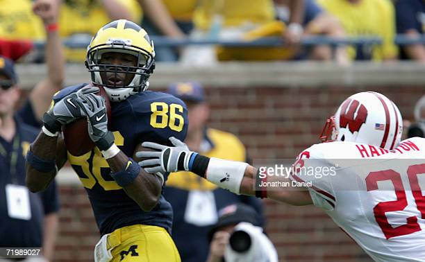 Mario Manningham of the Michigan Wolverines catches a pass in front of Zach Hampton of the Wisconsin Badgers during the game on September 23 2006 at...