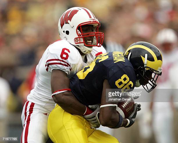 Mario Manningham of the Michigan Wolverines is tackled by Jack Ikegwuonu of the Wisconsin Badgers after catching a pass on September 23 2006 at...