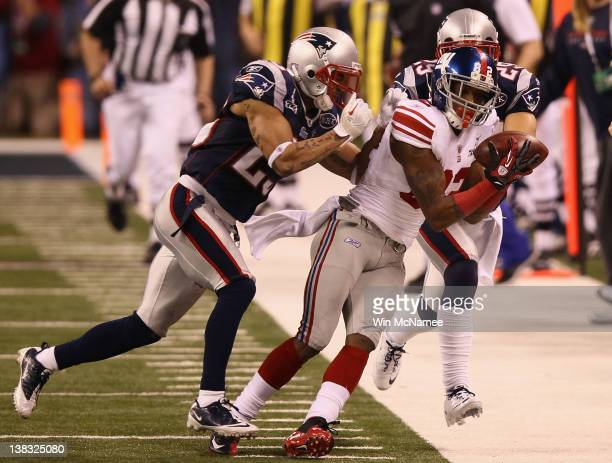 Mario Manningham of the New York Giants makes a catch on the sidelines against Patrick Chung and Sterling Moore of the New England Patriots for a...