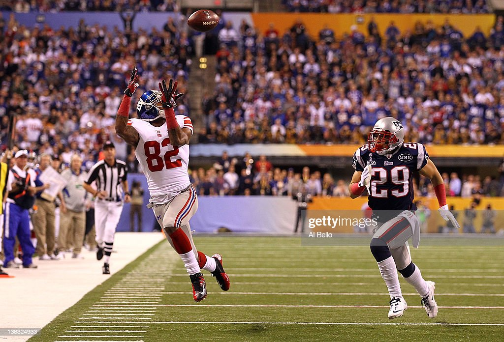 Mario Manningham #82 of the New York Giants makes a catch out of bounds over Sterling Moore #29 of the New England Patriots in the fourth quarter during Super Bowl XLVI at Lucas Oil Stadium on February 5, 2012 in Indianapolis, Indiana.