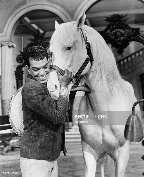 Mario Moreno Reyes hugging white stallion in a scene from the 1960 film Pepe