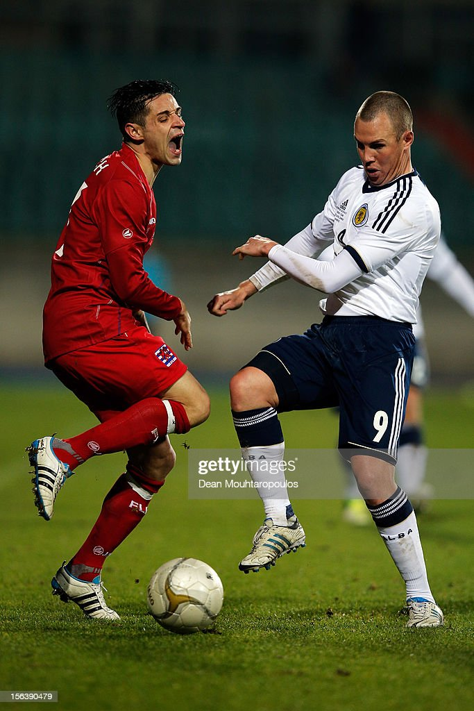 Mario Mutsch of Luxembourg is tackled and fouled by Kenny Miller of Scotland during the International Friendly match between Luxembourg and Scotland at Stade Josy Barthel on November 14, 2012 in Luxembourg, Luxembourg.