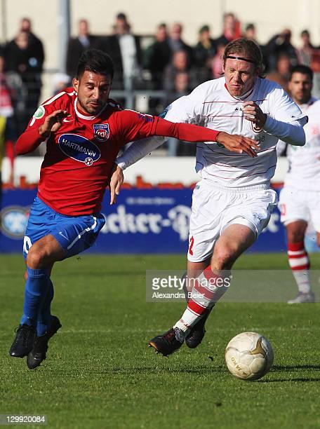 Mario Neunaber of Regensburg fights for the ball with Alper Bagceci of Heidenheim during the third league match between Jahn Regensburg and 1. FC...