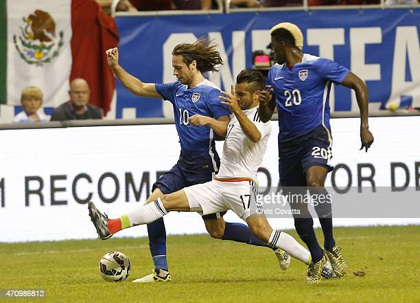 Mario Osuna of Mexico reaches for the ball between Mix Diskerud and Gyasi Zardes of the United States during an international friendly match at the...