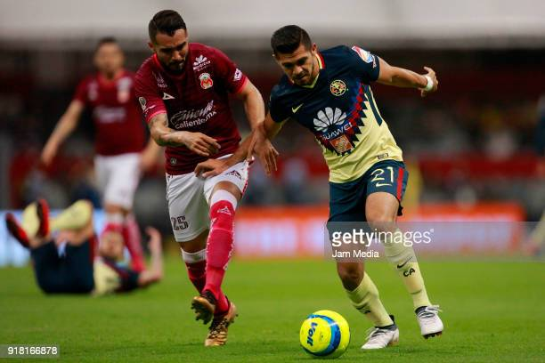 Mario Osuna of Morelia fights for the ball with Henry Martin of America during the 7th round match between America and Monarcas as part of the Torneo...