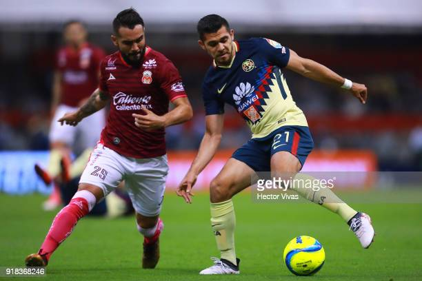 Mario Osuna of Morelia struggles for the ball with Henry Martin of America during the 7th round match between America and Monarcas as part of the...
