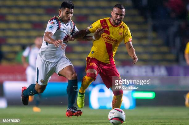 Mario Osuna of Morelia vies for the ball with Silvio Romero of America during their Mexican Apertura tournament football match at the Morelos stadium...