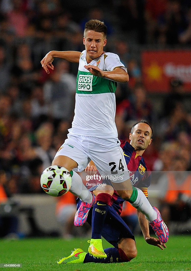 Mario Pasalic (L) of Elche FC beats Andres Iniesta of C Barcelona during the La Liga match between FC Barcelona and Elche FC at Camp Nou stadium on August 24, 2014 in Barcelona, Spain.