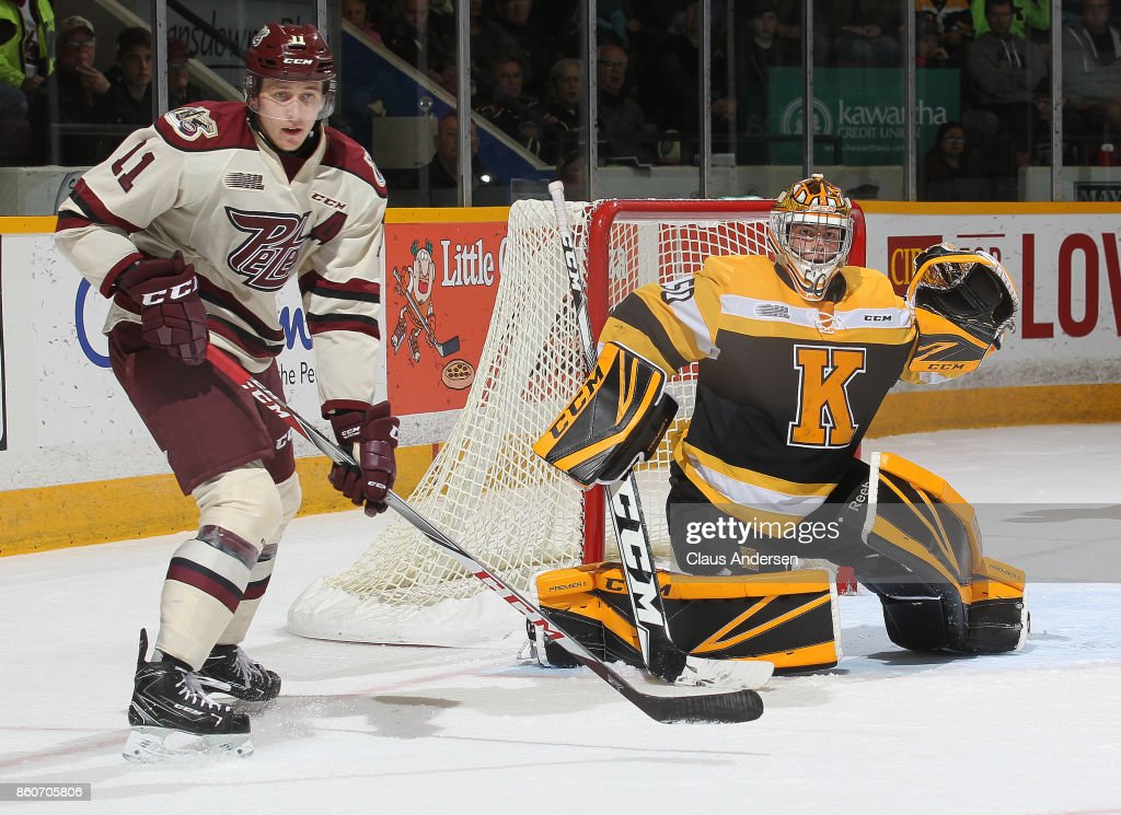 Mario Peccia #50 of the Kingston Frontenacs looks to face a shot with Zach Gallant #11 of the Peterborough Petes standing on his doorstep in an OHL game at the Peterborough Memorial Centre on October 12, 2017 in Peterborough, Ontario.