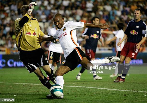Mario Regueiro of Valencia shoots past Timo Ochs of Salzburg during the third qualifying round of the UEFA Champions League match at the Mestalla...